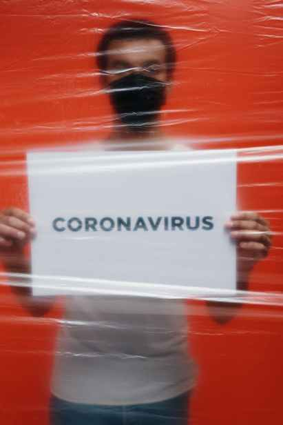 man in isolation holding a placard with coronavirus text